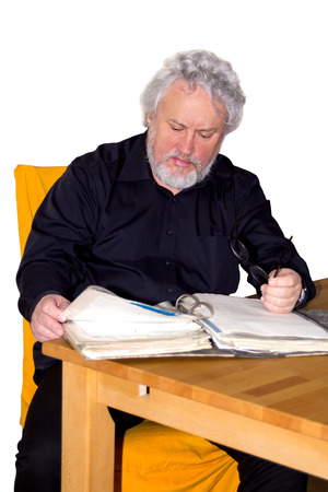 gray haired: Gray haired senior is checking out papers in a binder sitting at a table