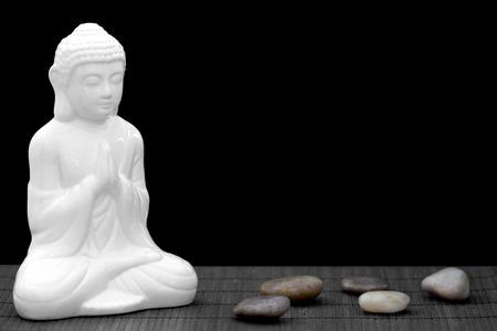 Figura bianca in posa di meditazione con ciottoli