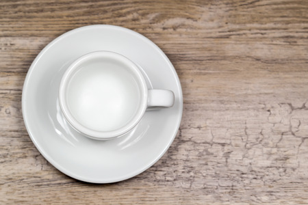 Empty clean espresso cup on wooden table with blurred background from above