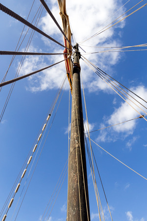 tilt views: View up a mast of an old sailing boat against slightly cloudy sky Stock Photo