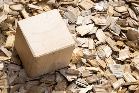Wooden cube lying in the garden on background of light mulch viewed from above