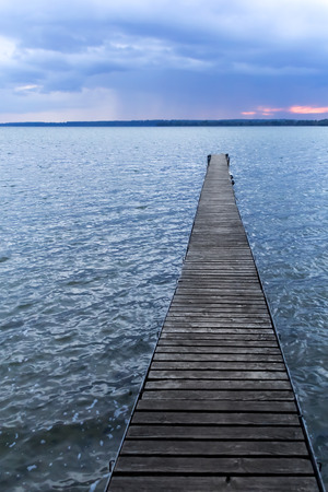 Vertical shot of a wooden pier at a lake just before night falls in Stock Photo