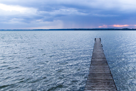 Horizontal shot of a wooden pier at a lake just before night falls in