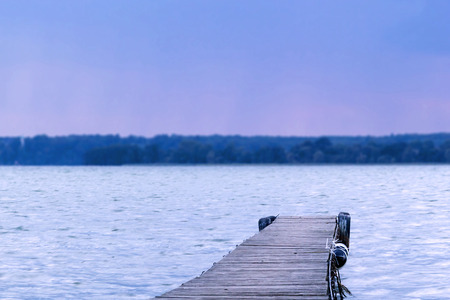 Dreamy tilt-shift picture of a pier leading into a lake Stock Photo