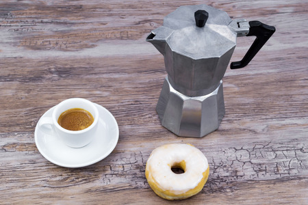 Espresso with a glazed donut on a wooden table from above with copy space