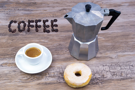 Espresso with a glazed donut on a wooden table from above with text coffee in coffee beans