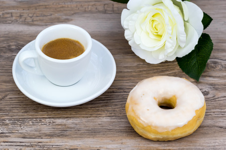 Espresso with a glazed donut and a white rose in blurred background on a wooden table from above