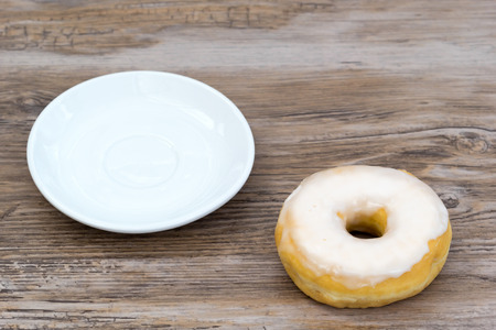 Glazed donut next to an empty plate from above - foodshot with slightly blurred background and copy space Stock Photo