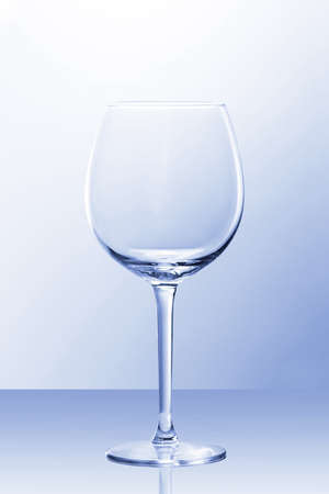 An empty red wine glass in slightly blue light with a reflection from POV