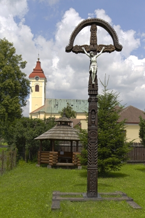 Photo of the old hand-carved and painted wooden crucifix  with the church in the background. This type of cross is typical for the region Detva Slovakia Stock Photo - 18281447