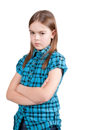 Angry young girl, isolated on white background, in blue modern checkered shirt, with arms crossed Stock Photo