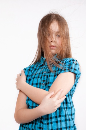 disheveled: Sadly disheveled young girl, isolated on white background, in blue modern checkered shirt, with arms crossed