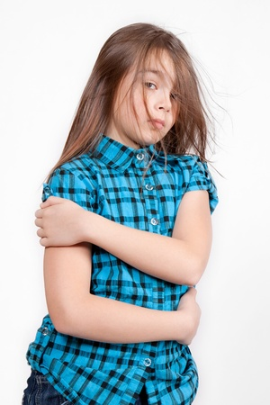 Disheveled young girl, isolated on white background, in blue modern checkered shirt, with arms crossed photo