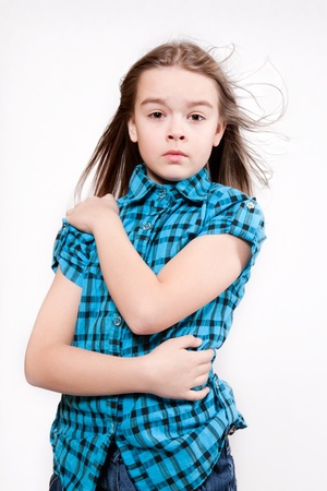 disheveled: Disheveled crying young girl, isolated on white background, in blue modern checkered shirt, with arms crossed Stock Photo