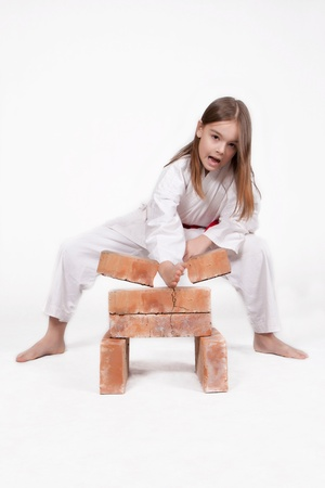 Karate girl in kimono breaks bricks with his hand, isolated on white background
