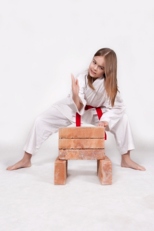 Karate girl in kimono breaks bricks with his hand, isolated on white background photo