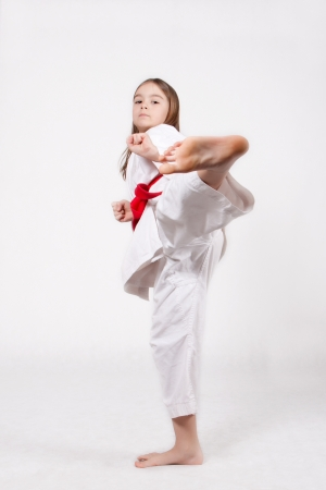 Karate young girl in a kimono with a red belt kicking up, isolated on white background photo