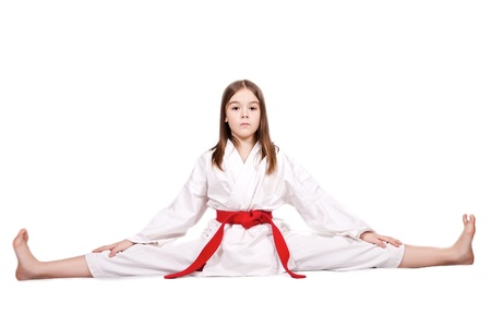 Karate young girl in a kimono with a red belt doing the splits, isolated on white background Stock Photo