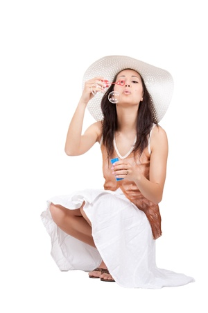 Brunette woman in white sun hat in a white dress on a white background, is squatting and blowing soap bubbles photo