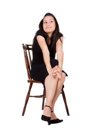 A woman in a black dress on a chair makes grimaces, isolated on white background