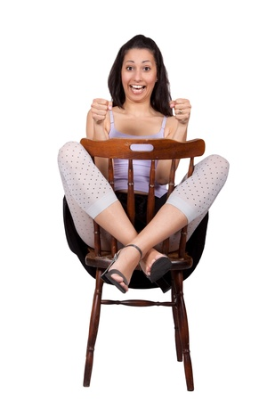 Long-haired brunette woman is sitting on a chair with legs raised, simulates driving a car, isolated on white background photo