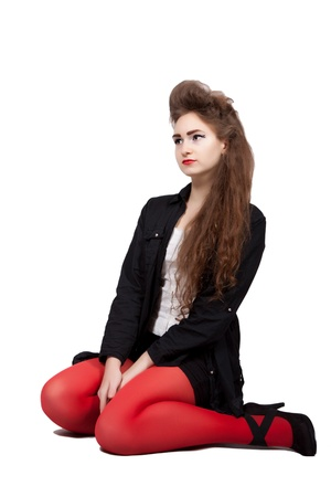 teenage girl dress: Teenage girl in black and red dress sitting on the ground is thoughtful, isolated on white background