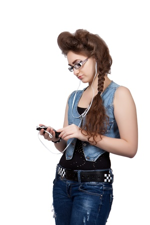 Teenage girl in a blue jeans clothes listening to music on the phone, isolated on white background photo