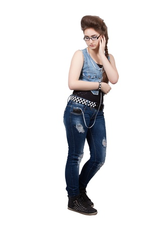 Teenage girl in a blue jeans clothes listening to music on the phone, isolated on white background