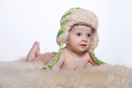 Little baby boy lying on stomach on woolen fleece on his head is cap on a white background
