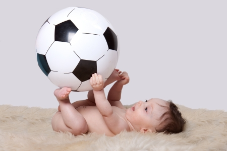 Little baby boy lying on her back on woolen fleece holding big soccer ball on white background photo