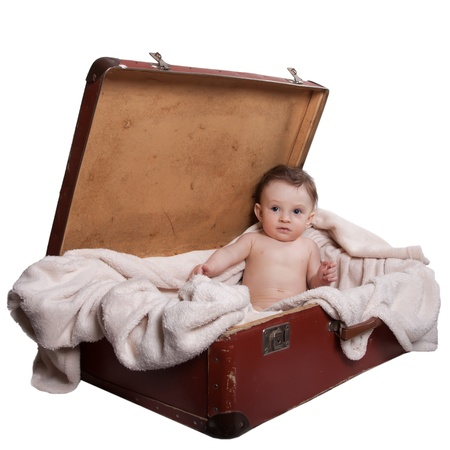 Little baby boy sitting with a blanket, in the old suitcases, on a white background photo