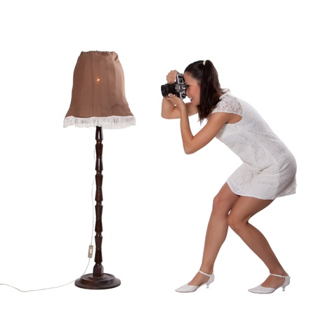 Retro woman in white dress, standing next to the old lamp and take pictures, with old camera isolated on white background photo
