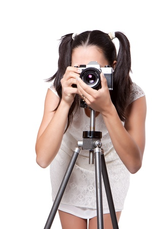 Retro woman in white dress, take pictures, with an old camera on a tripod isolated on white background photo