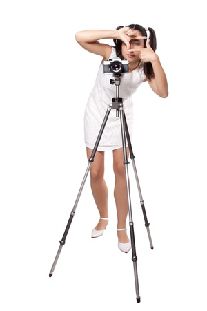 Retro woman in white dress, with an old camera on a tripod, creates a frame with her hands, isolated on white background photo