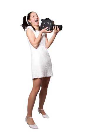 Retro woman in white dress, with an old film camera, laughing, isolated on white background photo