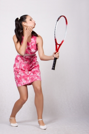 Retro girl in a pink dress holding a tennis racket as a mirror, check your makeup, isolated on white background Stock Photo - 20020007