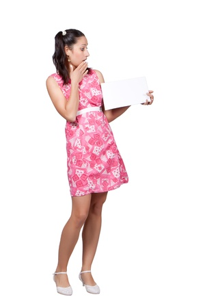 Retro girl in a pink dress, holding in his hands a blank sheet of paper for advertisement, isolated on white background