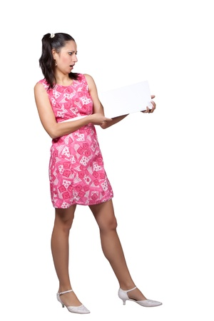 Retro girl in a pink dress, holding in his hands a blank sheet of paper for advertisement, isolated on white background photo