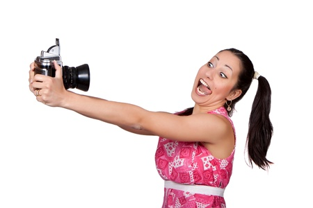Retro girl in a pink dress, holding in his hands an old camera, a photographer himself, makes a grimace, isolated on white background photo