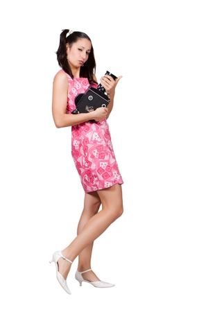 Retro girl in a pink dress, holding in his hands an old film camera and is sending the lips kiss, isolated on white background