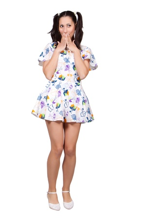 A girl with pigtails in colorful retro dress is embarrassed, covering her mouth with hands, isolated on white background Stock Photo - 20085873