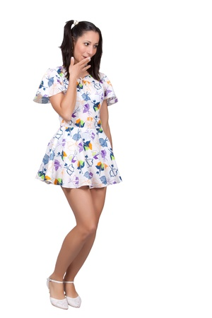 A girl with pigtails in colorful retro dress is embarrassed, covering her mouth with hand, isolated on white background photo
