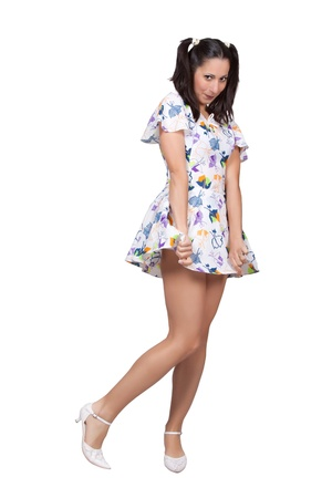 A girl with pigtails in colorful retro dress is embarrassed, she holds her skirt, isolated on white background Stock Photo - 20085867