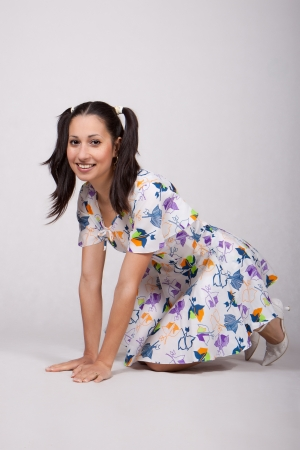 A girl with pigtails in colorful retro dress, kneeling hands and knees and laughs