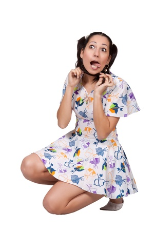 A girl with pigtails in colorful retro dress, is squatting and doing a grimace, isolated on white background