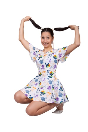 A girl with pigtails in colorful retro dress, is squatting and plays with braid, isolated on white background