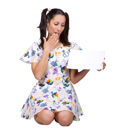 Woman in colorful retro dress kneeling on the ground, holding a blank paper, is embarrassed, isolated on white background