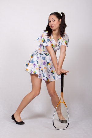 Woman in colorful retro dress, relies on squash racket, smiling