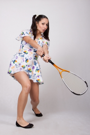 Woman in colorful retro dress, playing squash photo
