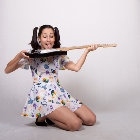 Woman in colorful retro dress, playing with her tongue on an electric guitar photo